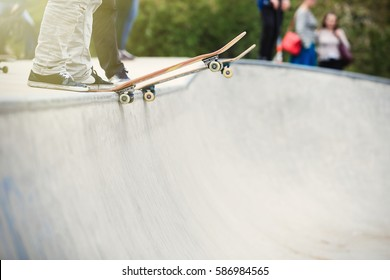 Skater boy standing on concrete ramp top in skatepark.Feet of skateboarder ready to ride on skate board in park.Popular extreme sport for young active people