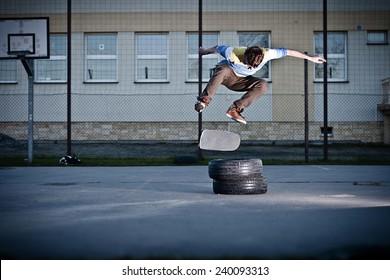 Skater doing the back side flip trick over the tyres.