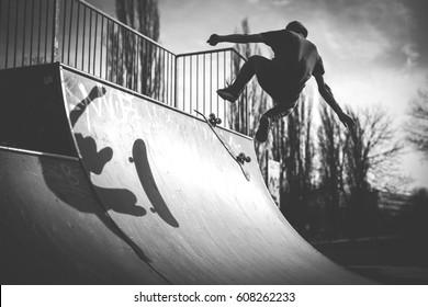 Skater doing a kickflip trick on ramp - black and white image