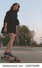 Skater girl with her longboard wearing a fashionable black balloon dress. Skateboarding is all about style and so is fashion. The two seem like a match made in heaven. Shot in an empty parking lot.