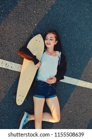 Skater girl lying down on asphalt surface of the road and enjoing summer warm weather after phisical activity