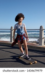 Skater girl on longboard, cruising doing tricks having fun carefree freedom summer holiday
