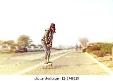 skater girl on street. smiling skateboarder  enjoying on long board on a sunny day.