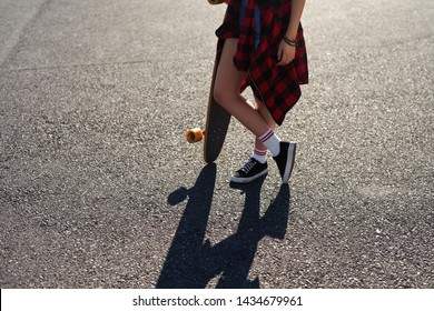 Skater girl woman with long board longboard, carefree teenage summer lifestyle anonymous