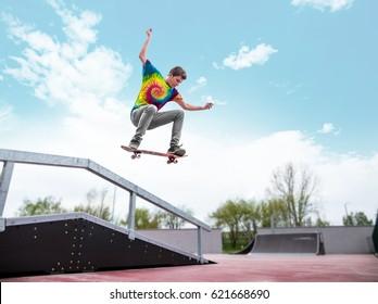 Skater jumping over handrail in skatepark