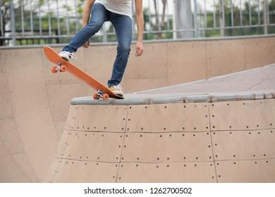 skater legs skating on ramp at skatepark