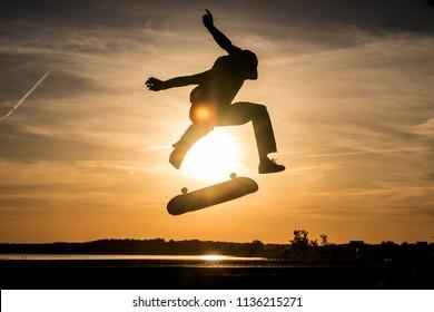 Skater make trick kickflip against the beautiful orange sunset