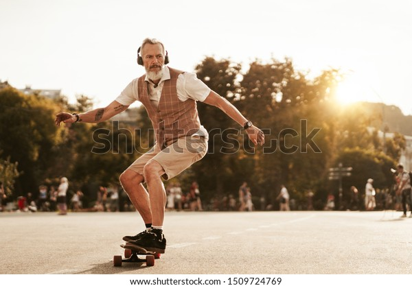 Skater posiert bei Sonnenuntergang in der Stadtstraße. Stilvoller Hipster-Mann mit Langboard-Fahrt auf Baugrundhintergrund. Porträt des männlichen Sportmodells im urbanen Stil. Reisende. Tourist