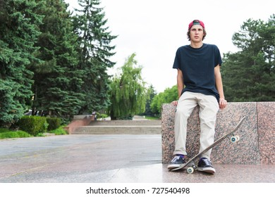 Skater sits with his back and thinks next to the skateboard
