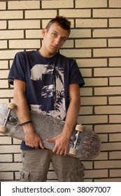 skater standing in front of a brick wall
