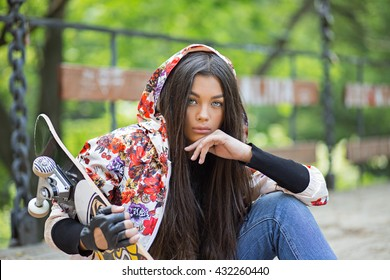 Skater, teenager with skate. Closeup portrait head shot beautiful brunette young woman  holding skate sitting on woody bridge background. Positive human emotion face expression feeling life concept