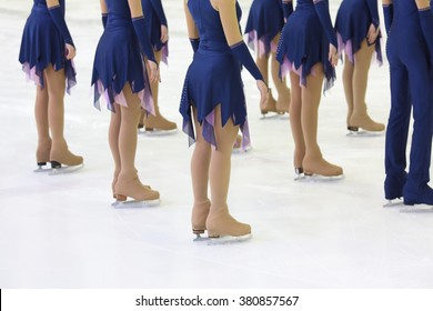 Skaters in beautiful costumes and skates on the ice in the sports complex, view below waist