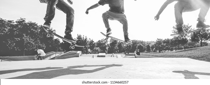 Skaters jumping with skateboard in city park - Young skate guys performing tricks and skills - Extreme sport and youth lifestyle concept - Main focus on left man - Black and white editing