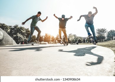 Skaters jumping with skateboard in city skate park - Young guys performing tricks and skills at sunset in suburb contest - Extreme sport and youth lifestyle concept - Main focus on left guy