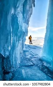 Skating man near ice grotto on lake Baikal