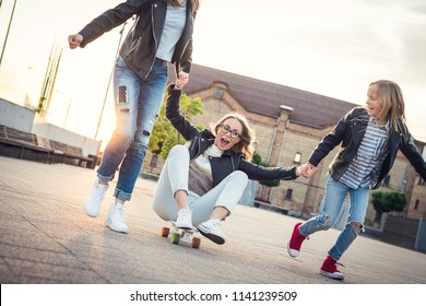 Skating. Mother with daughters are having fun and skating in the city