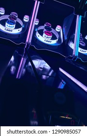 Skee Ball game in dark room with neon pink and blue lighting and reflections.