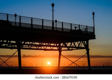 SKEGNESS, ENGLAND - JUNE 8: The end of Skegness pier, at sunrise, in June. Wind farm can be seen in the distance. In Skegness, Lincolnshire, England on 8th June 2015.