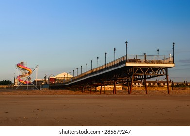 SKEGNESS, ENGLAND - JUNE 8: Skegness pier, the beach, and the fair ground, early morning, in June. In Skegness, Lincolnshire, England on 8th June 2015.