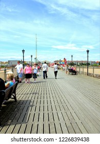 Skegness, Lincolnshire, UK. July 16, 2014. Holidaymakers enjoying walks looking towards the town from the end of the pier at Skegness, Linconshire, England, UK.