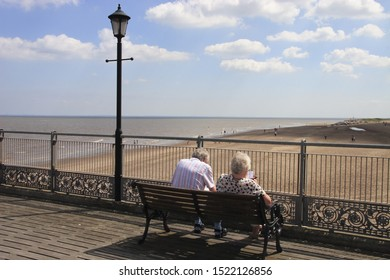 Skegness lincs 24th much 2009 elderly couple sitting on a bench looking across at the beach from Skegness pier