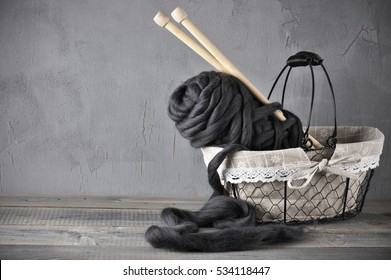 Skein of black super chunky woolen yarn with needles in rustic wire basket against gray background.