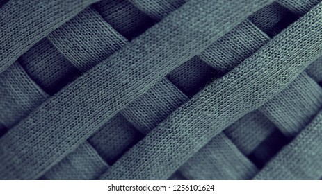 Skein of gray knitted yarn close-up. macro photography background texture pattern weave fiber textile fabric. strips of fabric are interwoven on a reel.