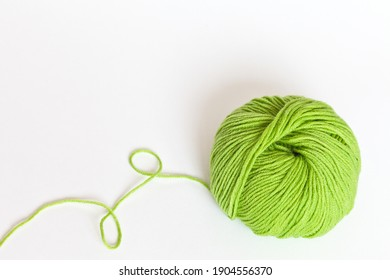 A skein of light green yarn for hand knitting on a white background. Spring handicrafts: crochet, knitting and embroidery. DIY concept. Empty space for text, close-up, mock up, top view