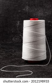 A skein of white thread on a black background. Copyspace