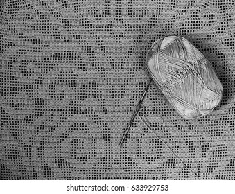 Skein of yarn and a hook lying on fillet lace. Black and white photo