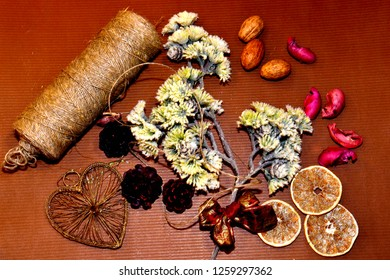 a skein of yarn, an iron heart, slices of lemon, cones and white shiny flowers for making a winter composition.