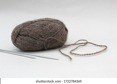 skein of yarn with knitting needles on a gray background