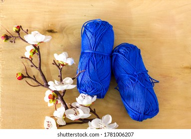 skeins of cotton yarn for knitting on a light wooden background with a sprig of spring white flowers