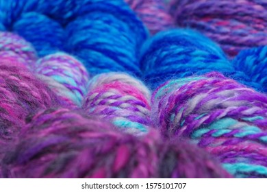 Skeins Of Hand Spun Yarn In Pink, Blue, Green, Purple, Grey, And Turquoise - Shown Sideways