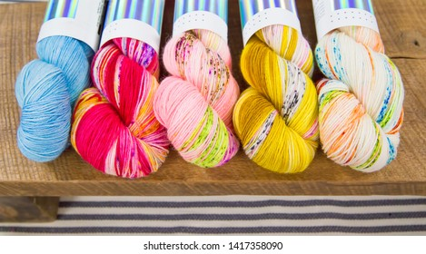 Skeins of vibrant variegated yarn lined up on a rustic wooden table