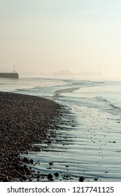 Skeletal West Pier appearing through sea mist at low tide on Brighton beach