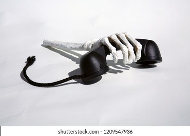 Skeleton arm holds onto a Telephone Reciever. On hold forever. Isolated on white. room for text. telephone call