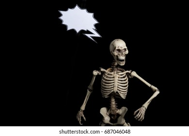 Skeleton with black background and paper speech bubble