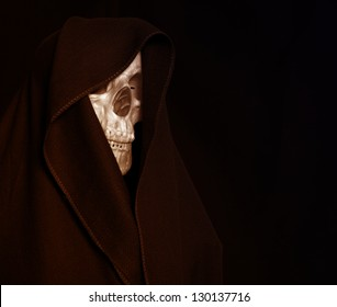 Skeleton in a black hood. Mystical image.
