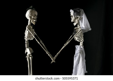 Skeleton bride and groom on a black background.
