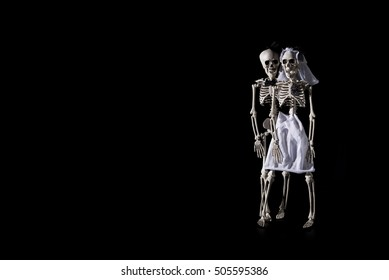 Skeleton bride and groom on a black background with negative space.