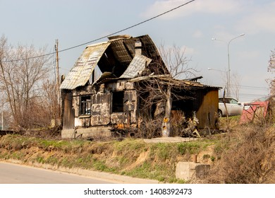 The skeleton of a burnt wooden house, a dwelling house after a fire, without treatment. Ruined village house, charred windows, hollowed roof, arson, accident