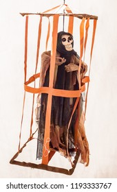 Skeleton dressed as a monster in a hanging cage.