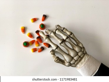 Skeleton hand reaching for candy corn mix