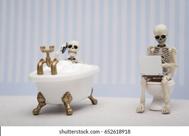 A skeleton having a phone call while having a bubble bath while other skeleton sitting on water closet with laptop on his lap