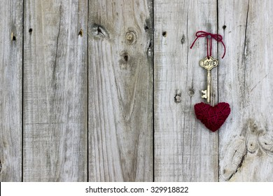 Skeleton key with Love and red rope heart hanging on rustic wood background