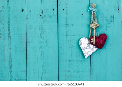 Skeleton key, red rope heart and silver tin heart hanging on antique rustic teal blue wood door; Valentines Day, Mothers Day and love concept background with painted wooden copy space