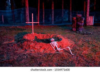 Skeleton near fresh grave with an established cross