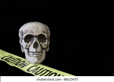 Skeleton on black background with yellow caution tape. Copy space.