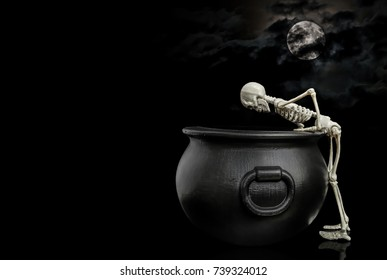 Skeleton Peaking In Cauldron / Halloween skeleton leaning over and looking inside a witches cauldron under a nice moon covered with dark clouds